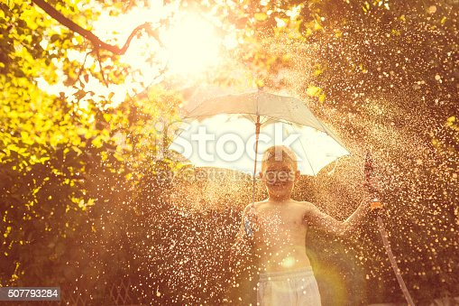 Boy splashing with water in garden on summer day, holding umbrella.