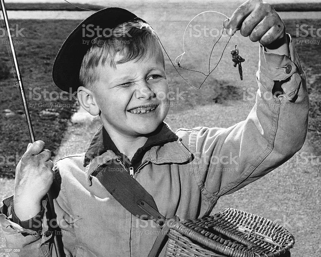 Boy squinting at baited hook royalty-free stock photo