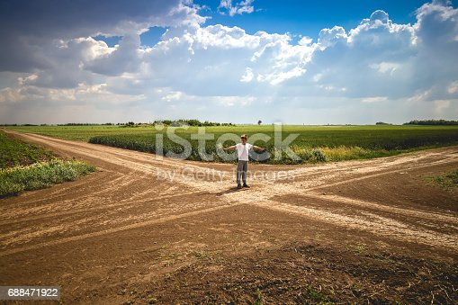 8 year boy standing at crossroad in path and pretending to regulate invisible traffic. Crossroad is surrounded by vast fields of wheat, rye and corn.
