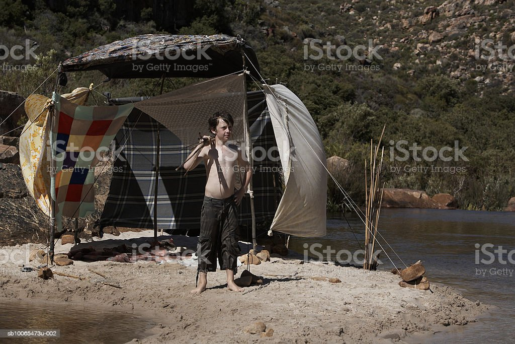 Boy (10-11) standing beside tent by stream royalty free stockfoto