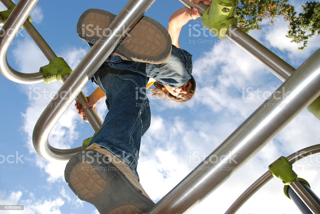boy standing high up on a climbing frame royalty-free stock photo