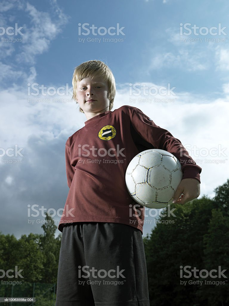 Boy (8-9 years) standing holding soccer ball, portrait, low angle view foto de stock libre de derechos
