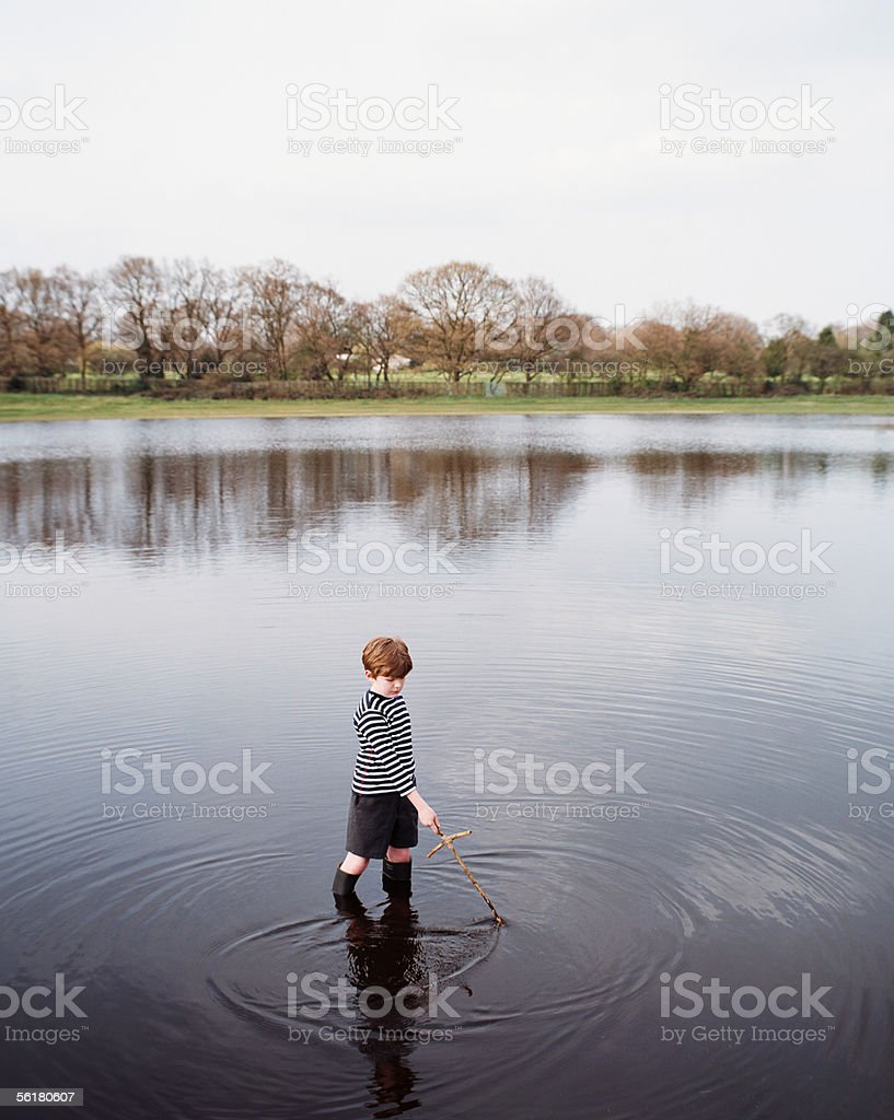 Boy standing in a lake stock photo