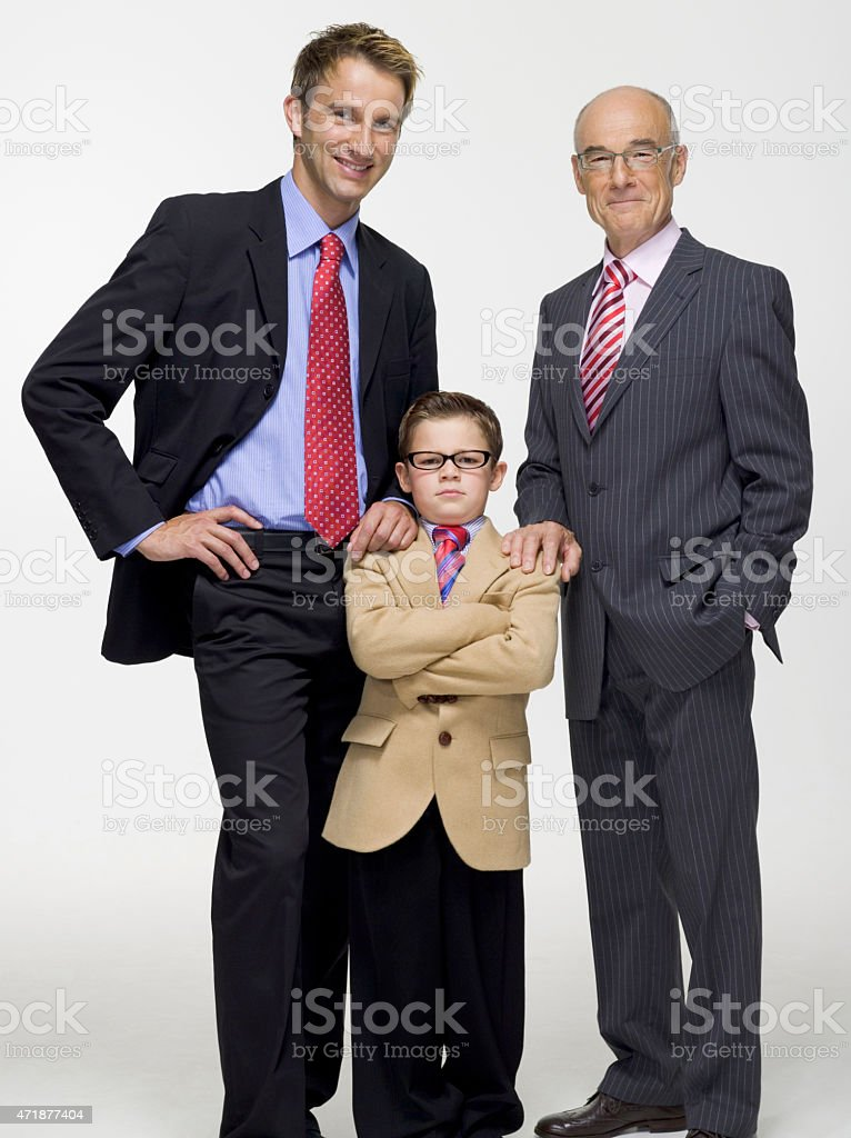 Boy standing in business attire with father and grandfather stock photo