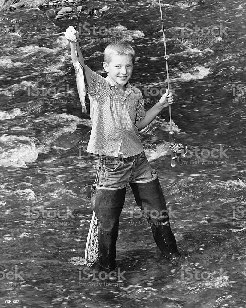 Boy standing in creek, holding up fish on end of fishing line royalty free stockfoto
