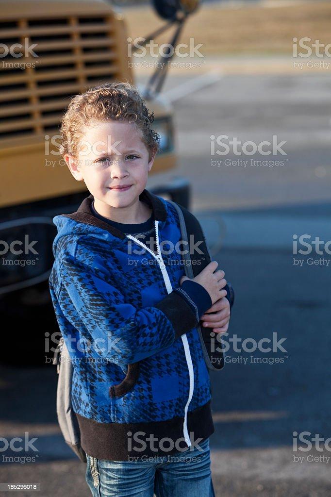 Boy standing in front of school bus stock photo