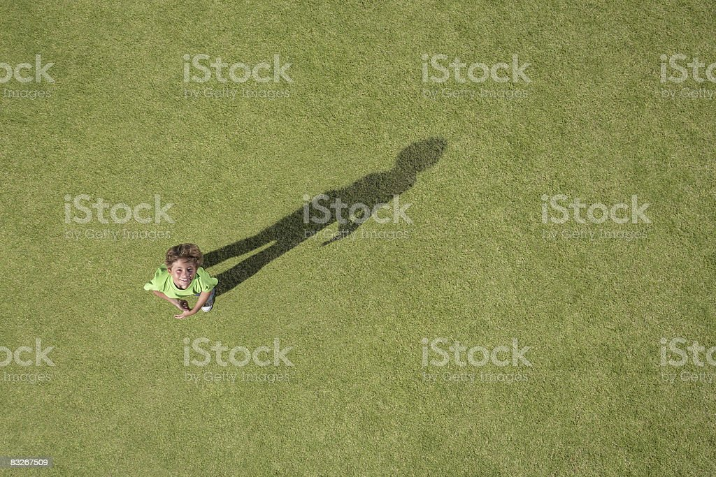 Boy standing in grass looking up stock photo