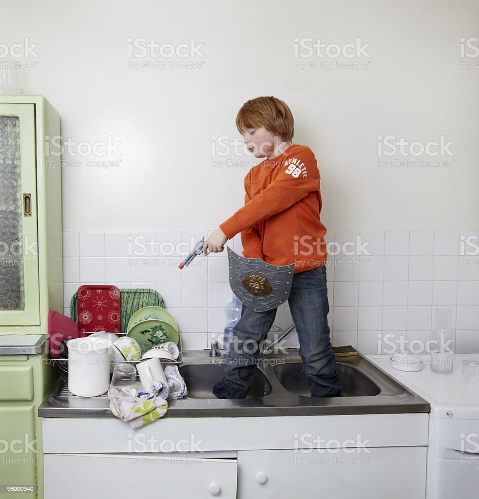boy standing in sink shooting the dishes royalty-free stock photo