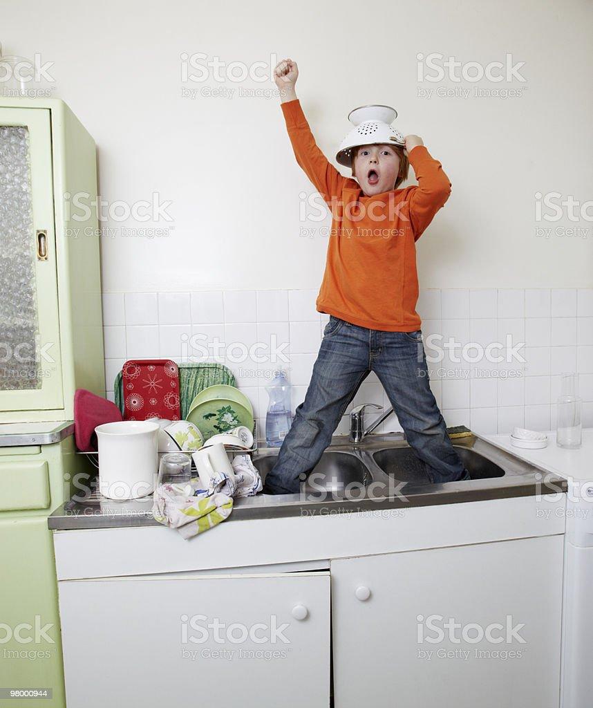 boy standing in sink with colander helmet royalty free stockfoto