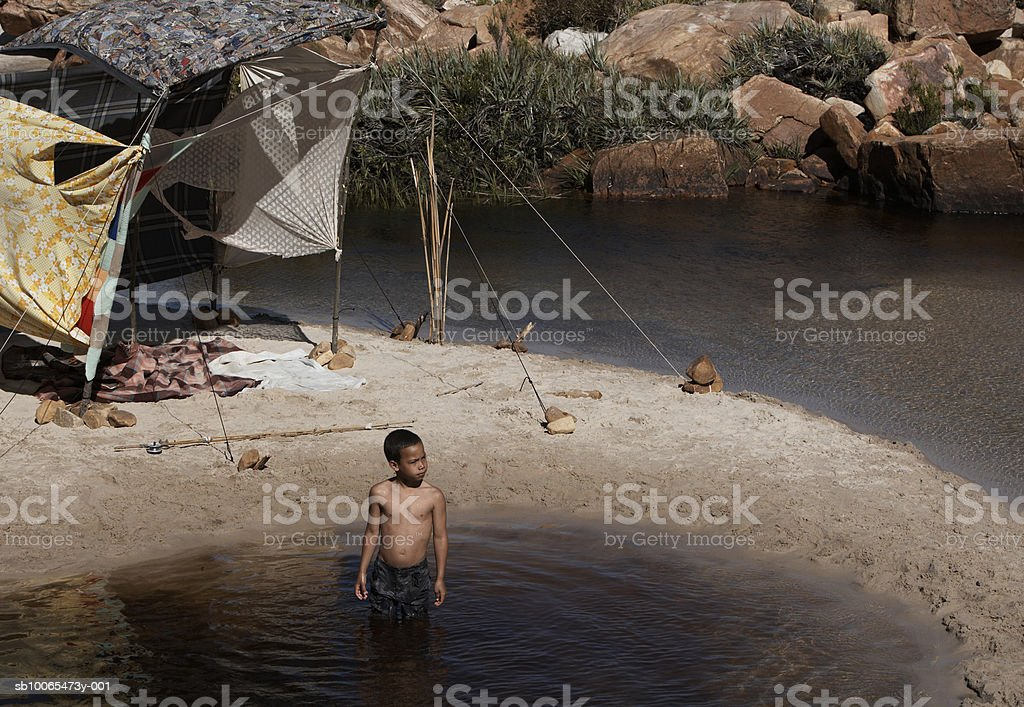 Boy (6-7) standing in water by tent, elevated view royalty-free stock photo