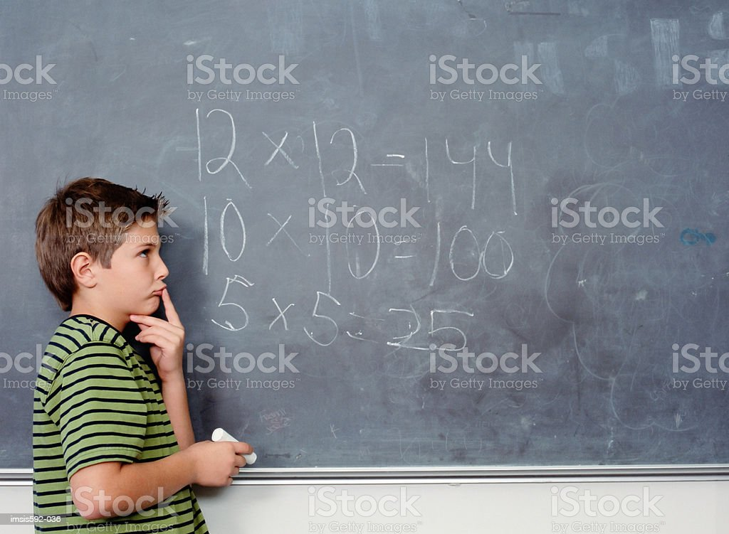 Boy standing near blackboard 免版稅 stock photo