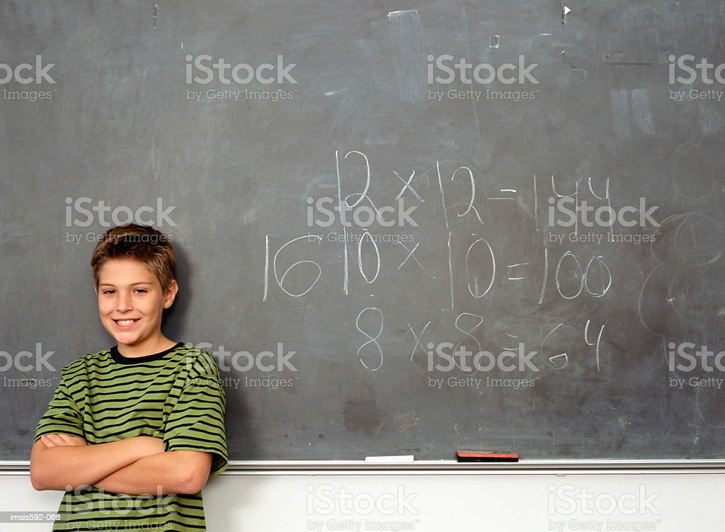 Boy standing near blackboard royalty-free stock photo