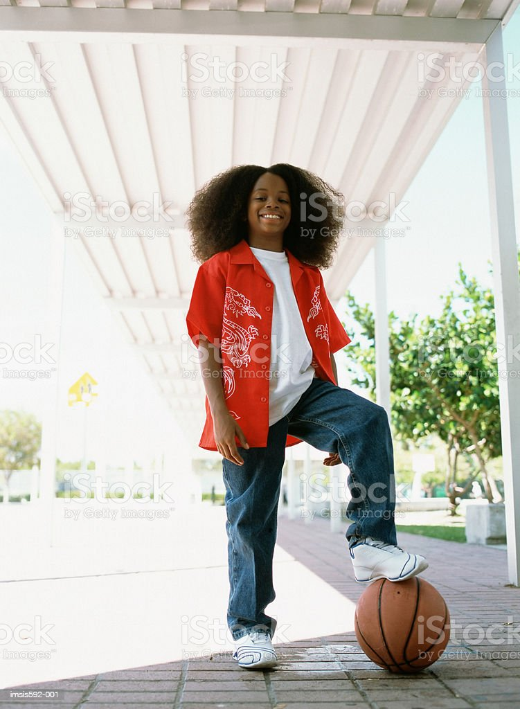 Boy standing on basketball royalty free stockfoto