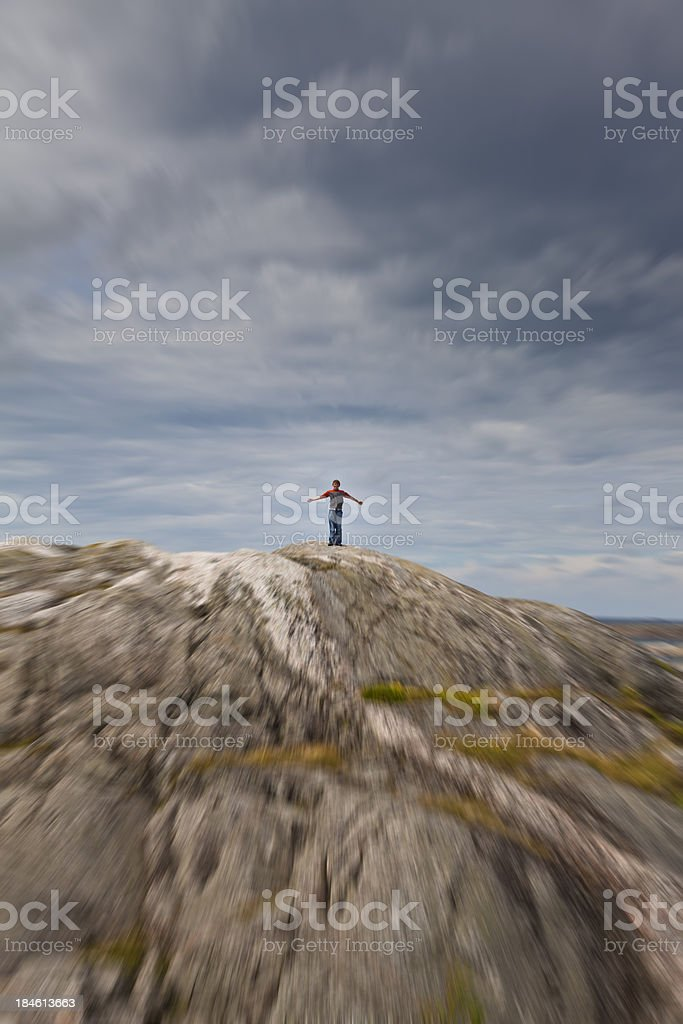 Boy standing on broody hillside zoomed blue stock photo