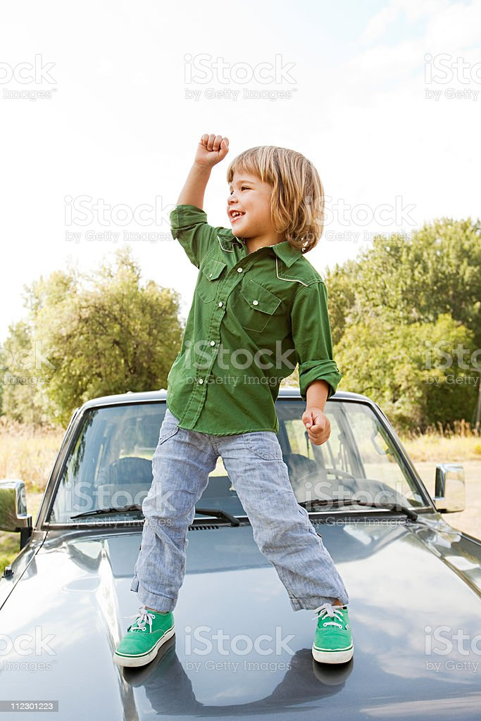 Boy standing on hood of car royalty-free stock photo