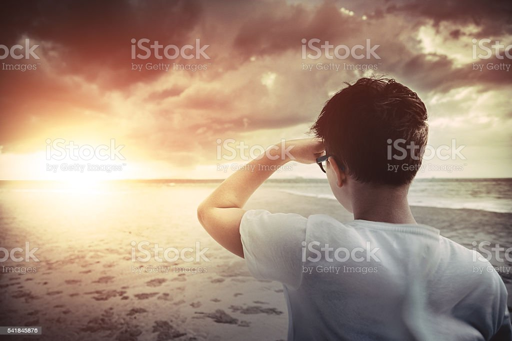 Boy standing on the beach at sunset and looking forward stock photo