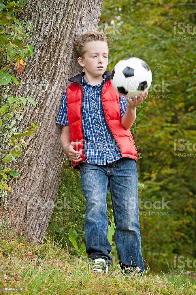 Boy standing with a soccer ball by the tree (V) royalty-free stock photo