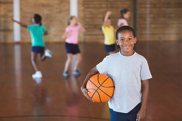 Boy standing with ball in basketball court stock photo