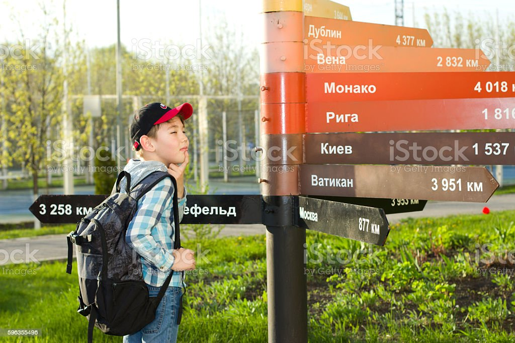 boy stands near the column with pointers to the cities royalty-free stock photo