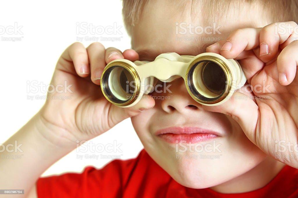 Boy stares through binoculars Стоковые фото Стоковая фотография