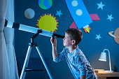 Curious boy using telescope to explore moon surface at night in his bedroom. Young child using telescope to see remote galaxy from room with decorated wall with rocket, planets, stars and cardboard solar system. Passionate kid in pajamas looking at stars using telescope, astronomy and stargazing concept.