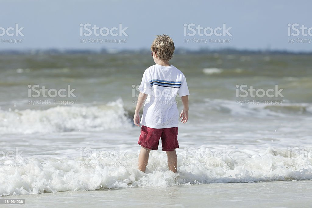 Boy Stepping into Ocean Surf stock photo