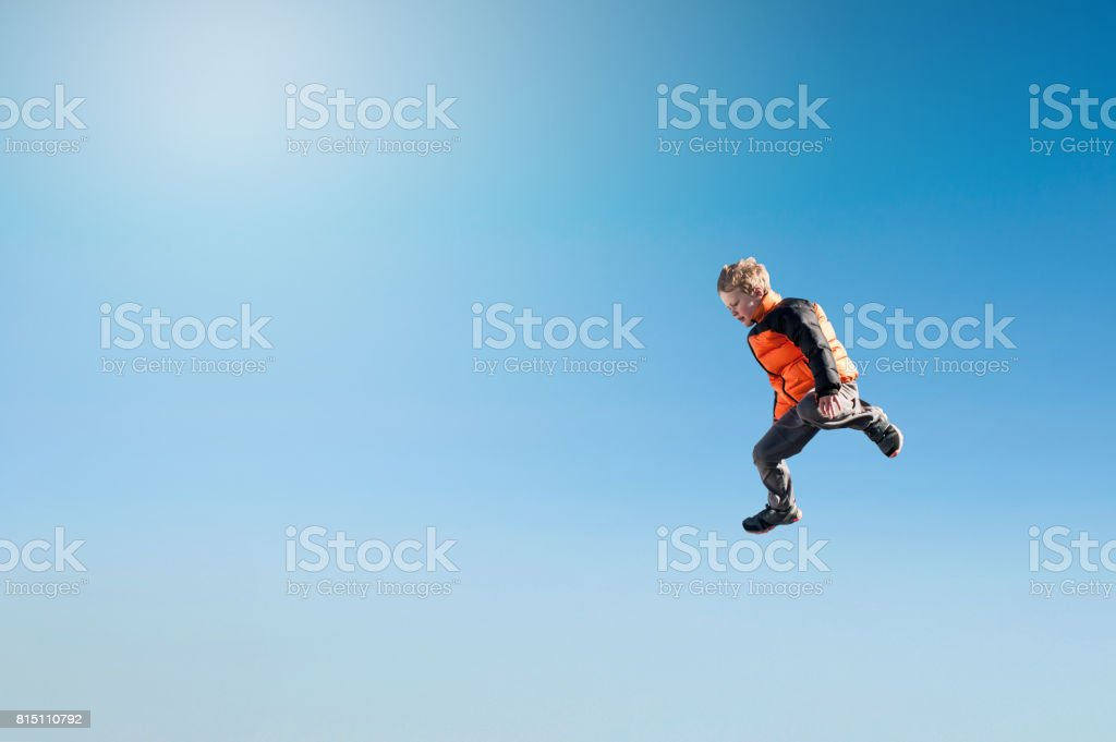 Boy stepping off Flying in blue sky stock photo