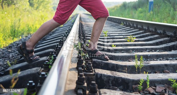 Boy in red shorts with stained feet steps over the rails of the railway, being exposed to danger