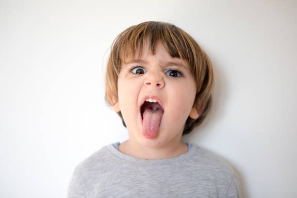 Boy Sticking Tongue Out Little boy portrait sticking out tongue stock pictures, royalty-free photos & images
