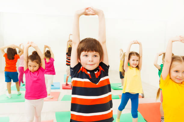 Boy stretching hands during sports lesson in gym stock photo