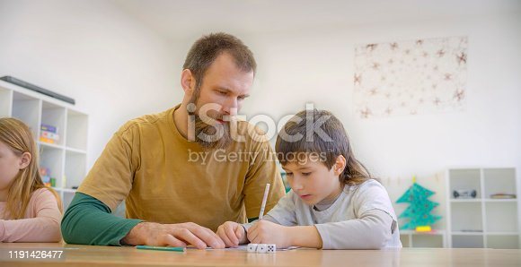 Teacher assisting student in classroom.