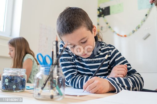 Boy writing on paper in classroom.