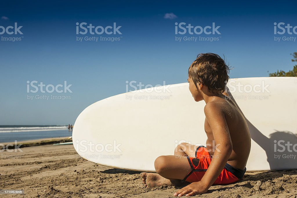 Boy surfer watching the waves in Costa Rica royalty-free stock photo