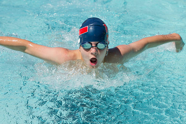 Boy Swimming Butterfly In Pool During Competitive Race stock photo