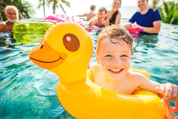 Boy swimming in a pool with family Boy swimming in a pool with family swimming pool stock pictures, royalty-free photos & images