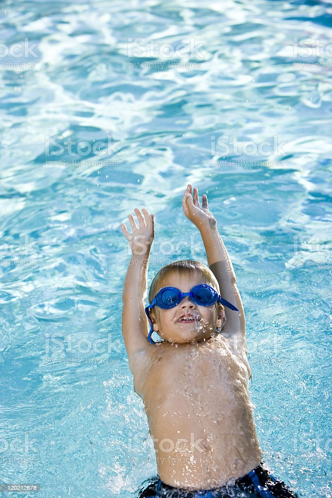 Boy swimming on his back in pool stock photo