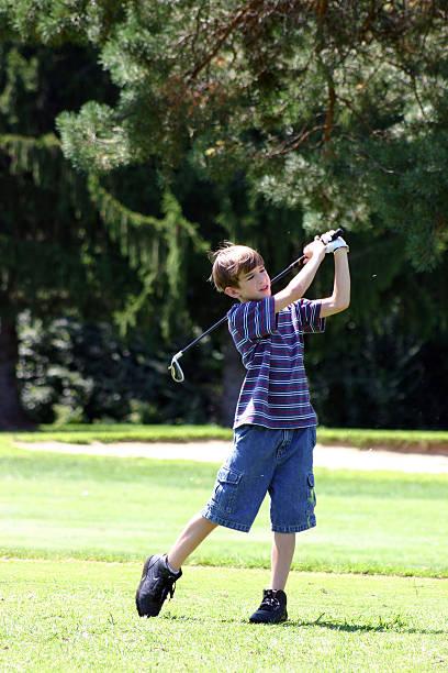 Boy swinging golf club stock photo