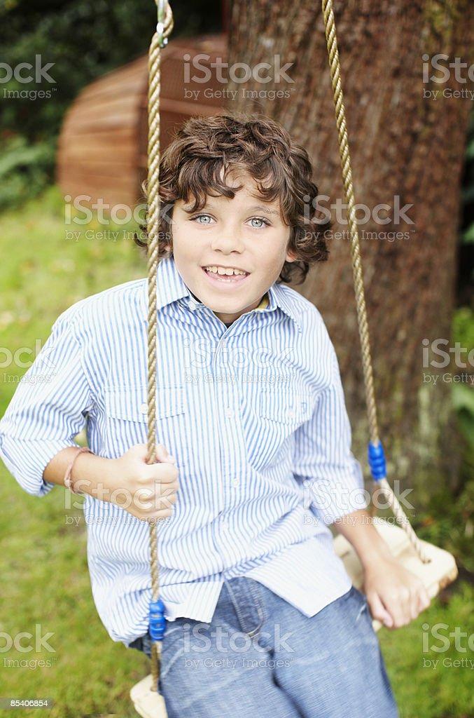 Boy swinging in backyard 免版稅 stock photo
