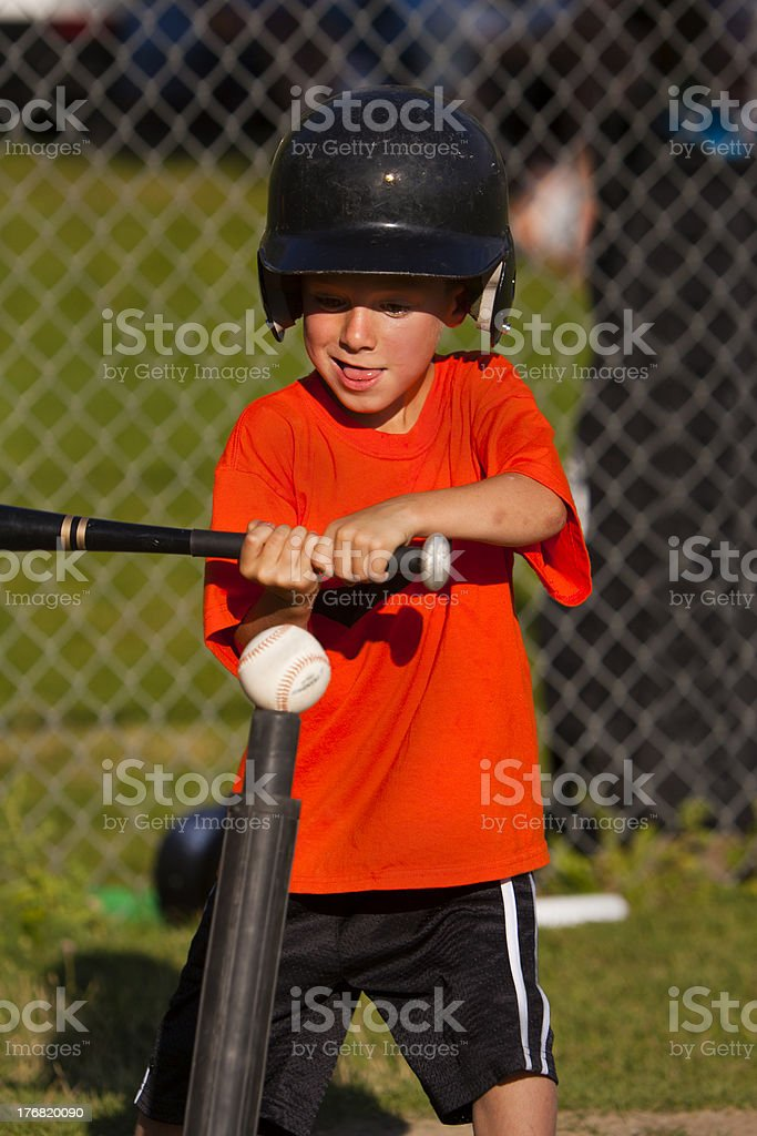 Boy swings bat at tee-ball stock photo