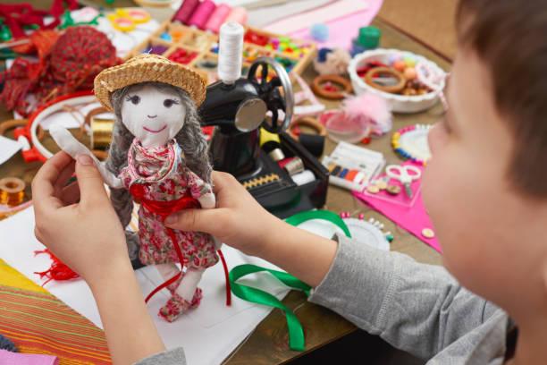 boy tailor learns to sew, dress for doll, handmade and handicraft concept - nähpuppen stock-fotos und bilder
