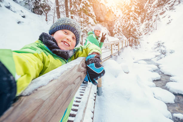 Boy take a selfie picture with his father in snow mountain canyon stock photo