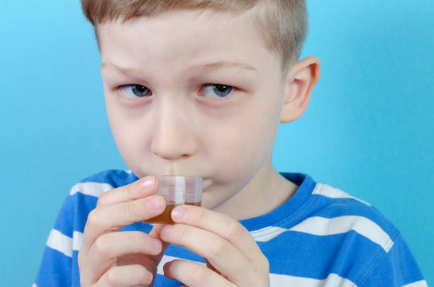 boy takes medicine syrup on blue background boy takes medicine syrup on blue background, closeup antipyretic stock pictures, royalty-free photos & images