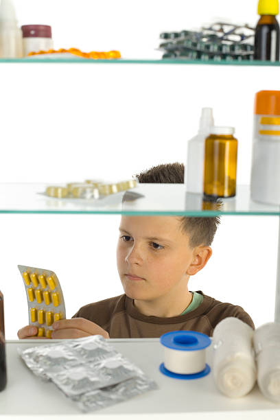 Boy takes yellow tablets from medicine cabinet stock photo