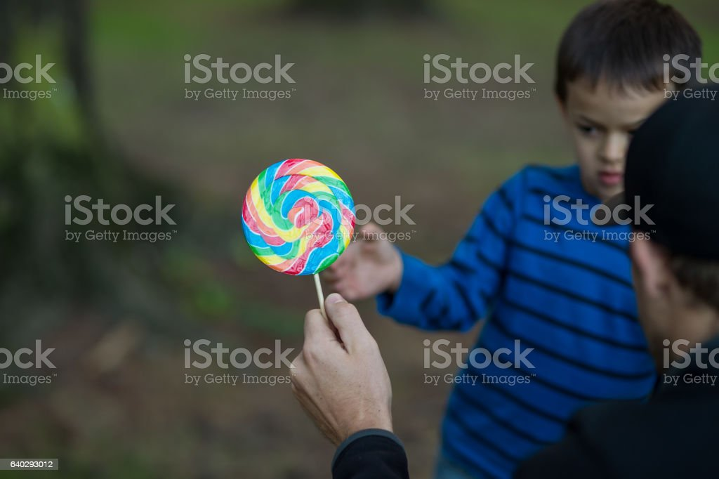 Boy taking candy from stranger stock photo