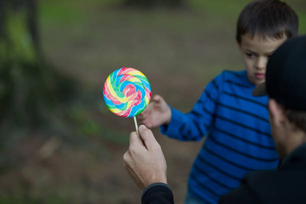 Boy taking candy from stranger Six or seven year old boy accepting lollipop from strange man. stranger stock pictures, royalty-free photos & images
