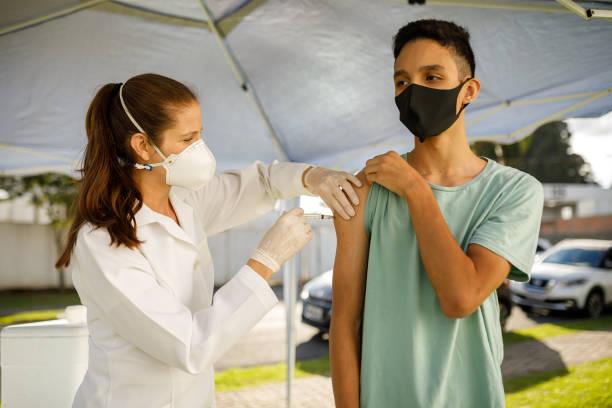 Boy taking covid 19 vaccine stock photo
