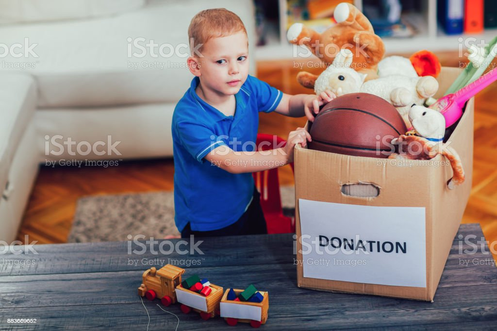 Boy taking donation box full with stuff for donate stock photo