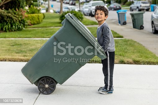 High quality stock photo of a young boy taking out the trash in an urban neighborhood.