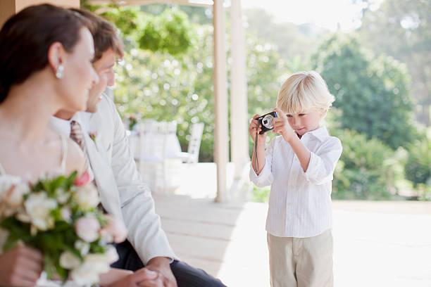 junge nimmt ein bild von braut und bräutigam - hochzeitsfeier mit kindern stock-fotos und bilder