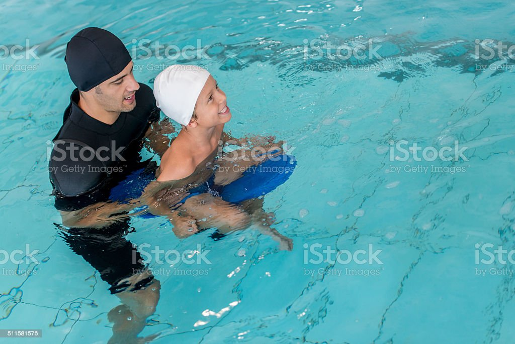 Boy taking swimming lessons stock photo